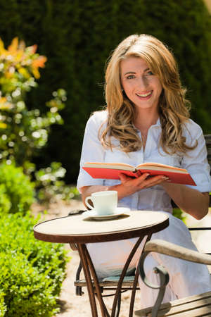 coffee hour: woman reading a book in the garden Stock Photo