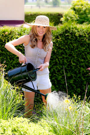 irrigate: woman pouring flowers in the garden with watering can