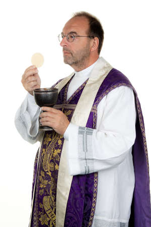a catholic priest with a chalice and paten at communion photo
