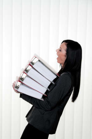 deprived women with stress and folders in the office photo