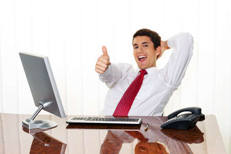 team spirit: a successful young manager sitting at a desk and smiles