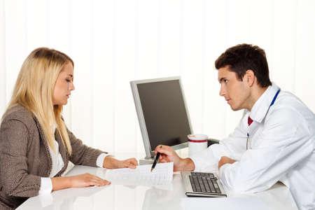 consulta médica: paciente consulta médica y médico hablando con un consultorio médico s Foto de archivo