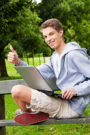ordinateur: a teenager with a laptop outdoors  sitting in the park mobile internet