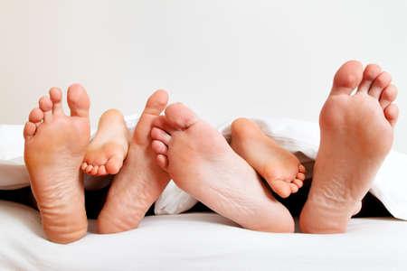 die Sohlen von einer Familie im Bett unter der Bettdecke
