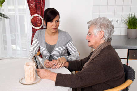 a young woman comforting a widow after death  grief counseling  photo