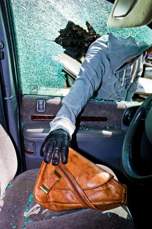 eingeschifft: ein Dieb stahl eine Handtasche aus einem Auto durch eine zerbrochene Seitenscheibe Lizenzfreie Bilder