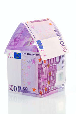 subsidy: a house built with money on a white background  savings, house building and home buying  Stock Photo