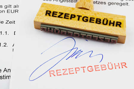 therapie: a stamp made of wood lying on a document  german inscription  prescription charges Stock Photo