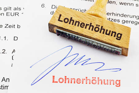 a stamp made of wood lying on a document  german inscription  wage increase Stock Photo