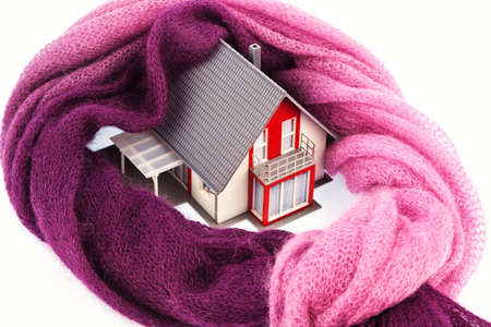 thermal: a model house is wrapped in a shawl  photo icon for thermal insulation and reduced heating costs  Stock Photo