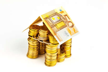 single familiy: a house made of coins and banknotes  photo icon for house construction and home loans Stock Photo