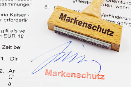 thesis: a stamp made of wood lying on a document  german inscription  brand protection