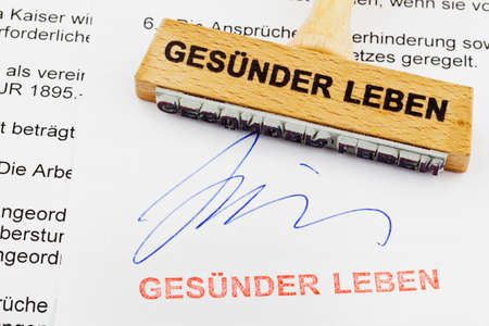 eat right: a stamp made of wood lying on a document  german inscription  live healthier Stock Photo
