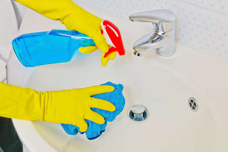 cleaned: the sink of a bathroom is cleaned with latex gloves
