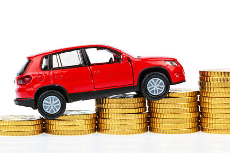 mileage: a model car and coins against white background, photo for price increases, fuel costs and car expenses