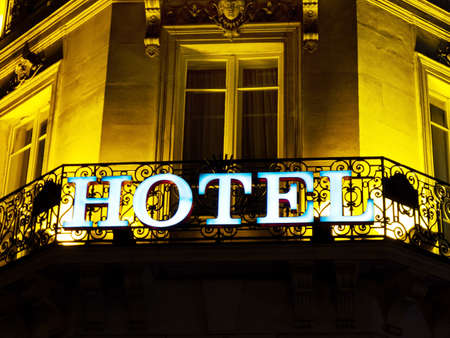hotel stay: the inscription on a neon light from hotelin paris, france at night