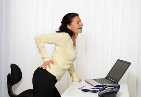 rheumatism: woman with back pain of the intervertebral disc in office work