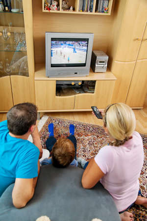 a family watching tv with tv photo