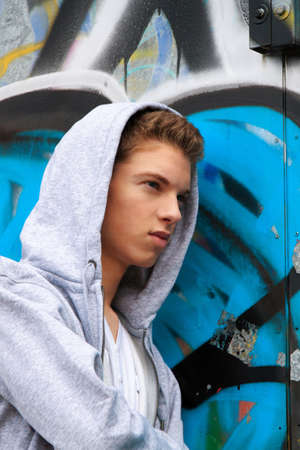 hip hop style: a cool-looking young man in front of graffiti