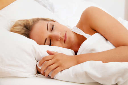 good night: una mujer joven y bonita durmiendo en cama, recuper�ndose