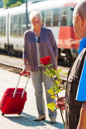 vital: mature vital elderly couple at the railway station  travel on holiday