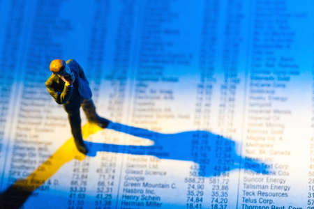 a small figure and the prices of shares in a newspaper  make money on the stock exchange  gains and losses in stock trading Stock Photo - 14181664