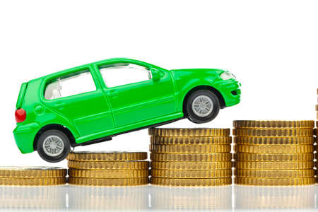 auto leasing: a model car is on coins  rising costs for gasoline car prices, insurance and taxes  Stock Photo