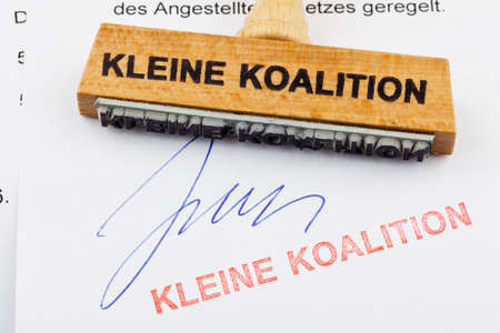 coalition: a stamp made of wood lying on a document  german inscription  small coalition