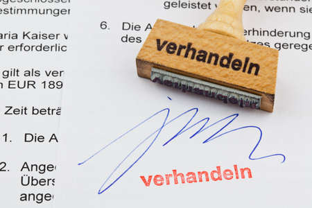 a stamp made of wood lying on a document  negotiate  german inscription photo