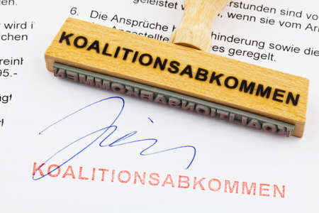 coalition: a stamp made of wood lying on a document  german inscription  coalition agreement
