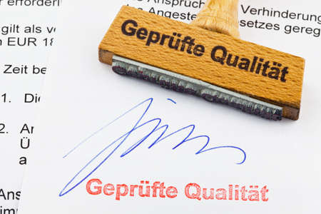 norm: a stamp made of wood lying on a document  german inscription  proven quality Stock Photo