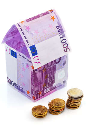 seem: a house built with money seem € on a white background. savings, house building and home buying. Stock Photo