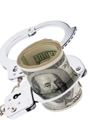 tax evasion: many dollar bills with handcuffs