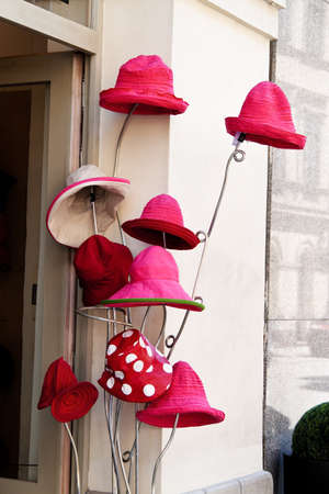 several red hats are waiting for buyers in front of a millinery