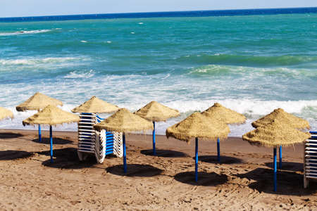 lull: empty deck chairs on a sandy beach by the sea in spain.