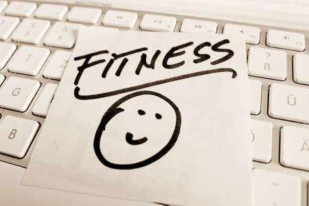 peoplesoft: a memo is on the keyboard of a computer as a reminder: fitness