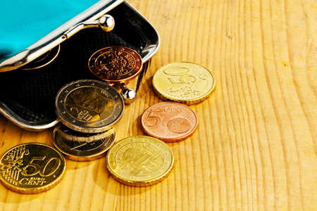 few: coins and an empty wallet with a few €. photo icon on debt and poverty