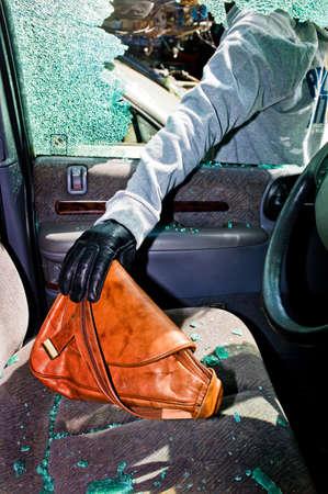 eingeschifft: ein Dieb stahl eine Handtasche aus einem Auto durch eine zerbrochene Seitenscheibe. Lizenzfreie Bilder