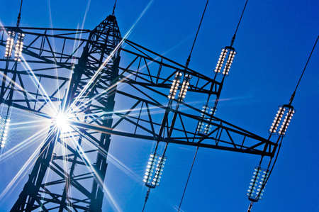 a high-voltage electricity pylons against blue sky and sun rays photo