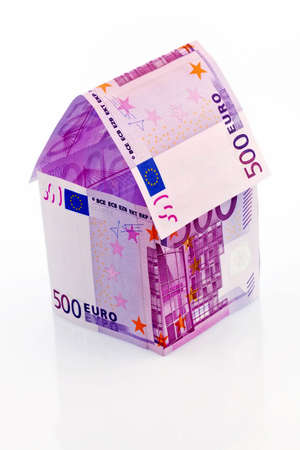 sponsorship: a house built with money seem € on a white background. savings, house building and home buying.