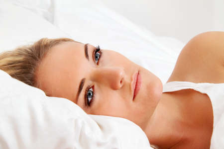 a young woman lies awake in bed  sleepless and thoughtful  photo
