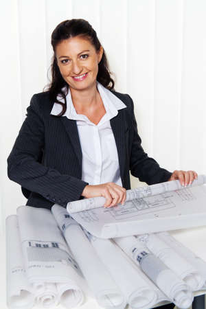 salaried worker: architect with building plan in the office  plans of a house are processed Stock Photo