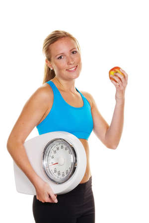 thinness: young woman with bathroom scale and apple  successful diet