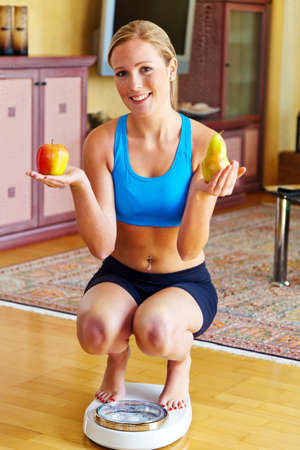 ideal: young woman with bathroom scale and apple  successful diet