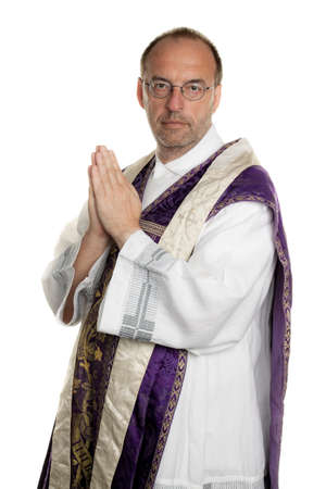 reverent: a catholic priest, while praying in church Stock Photo