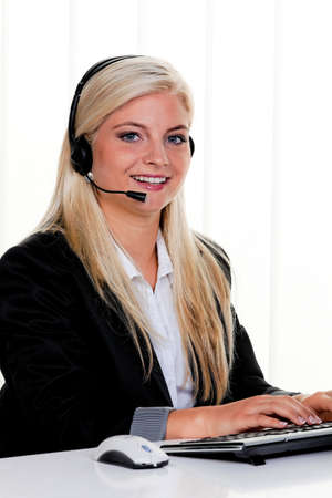 callcenter: young woman with headset at computer and hotline