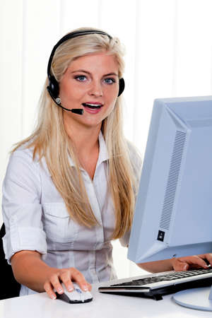 young woman with headset at computer and hotline  photo