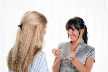 amigas conversando: dos mujeres en una conversación en la oficina de arbitsplatz