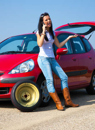 young woman with a flat tire on car photo