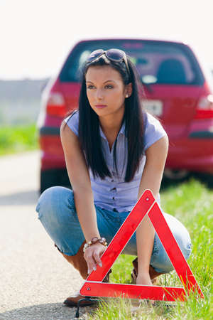 warning triangle: young woman with a warning triangle in case of breakdown Stock Photo